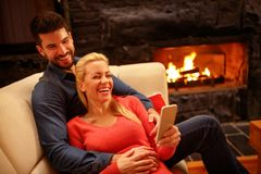 Couples heureux dans l'amour étreignant et à l'aide du téléphone portable Images libres de droits
