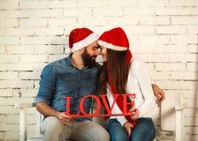 Couples heureux dans l'amour ainsi que le chapeau de Noël Photographie stock