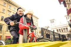 Couples heureux dans l'amour appréciant l'horaire d'hiver extérieur sur la bicyclette de vintage Photographie stock