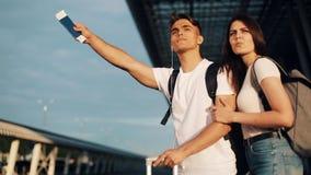 Couples heureux dans l'amour attrapant un taxi se tenant avec le bagage près de l'aéroport, voyageant Le concept du repos, vacanc banque de vidéos