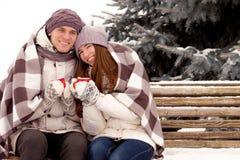 Couples heureux dans l'amour avec la tasse de café en parc en hiver Photographie stock