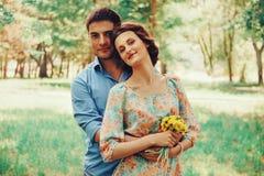 Couples heureux dans l'amour avec le bouquet des pissenlits jaunes Image libre de droits