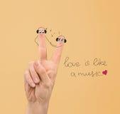 Couples heureux dans l'amour avec les visages peints dans des écouteurs Photo libre de droits
