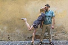 Couples heureux dans l'amour ayant l'amusement contre le mur de la maison Photographie stock libre de droits