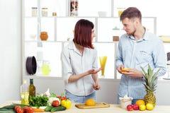 Couples heureux dans l'amour dans la cuisine faisant le jus sain à partir de l'orange fraîche Photographie stock