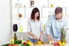 Couples heureux dans l'amour dans la cuisine faisant le jus sain à partir de l'orange fraîche Photo libre de droits