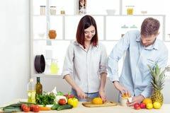 Couples heureux dans l'amour dans la cuisine faisant le jus sain à partir de l'orange fraîche Photos libres de droits
