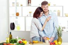 Couples heureux dans l'amour dans la cuisine faisant le jus sain à partir de l'orange fraîche Image libre de droits