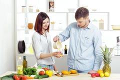 Couples heureux dans l'amour dans la cuisine faisant le jus sain à partir de l'orange fraîche Photographie stock libre de droits