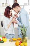 Couples heureux dans l'amour dans la cuisine faisant le jus sain à partir de l'orange fraîche Image stock