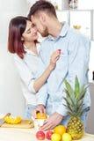 Couples heureux dans l'amour dans la cuisine faisant le jus sain à partir de l'orange fraîche Le couple embrasse Images stock