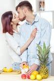 Couples heureux dans l'amour dans la cuisine faisant le jus sain à partir de l'orange fraîche Le couple embrasse Photos stock