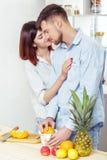 Couples heureux dans l'amour dans la cuisine faisant le jus sain à partir de l'orange fraîche Le couple embrasse Photographie stock