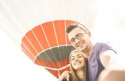 Couples heureux dans l'amour des vacances prenant le selfie au ballon à air chaud Photos libres de droits