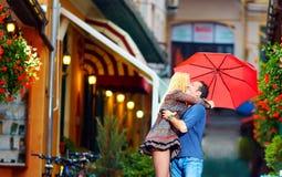 Couples heureux dans l'amour embrassant sur la rue colorée Photo stock