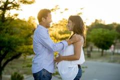 Couples heureux dans l'amour ensemble dans le paysage de parc sur le coucher du soleil avec le ventre et l'homme enceintes de fem Photos libres de droits