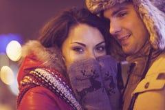 Couples heureux dans l'amour extérieur dans des lumières de Noël de soirée Image libre de droits