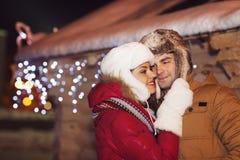 Couples heureux dans l'amour extérieur dans des lumières de Noël de soirée Photographie stock libre de droits