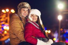 Couples heureux dans l'amour extérieur dans des lumières de Noël de soirée Photographie stock