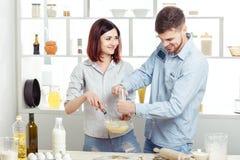 Couples heureux dans l'amour faisant cuire la pâte dans la cuisine Photo stock