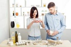 Couples heureux dans l'amour faisant cuire la pâte dans la cuisine Images libres de droits