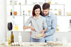 Couples heureux dans l'amour faisant cuire la pâte dans la cuisine Image stock