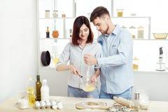 Couples heureux dans l'amour faisant cuire la pâte dans la cuisine Images stock