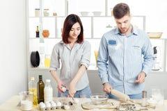Couples heureux dans l'amour faisant cuire la pâte dans la cuisine Photos libres de droits