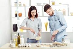 Couples heureux dans l'amour faisant cuire la pâte dans la cuisine Photographie stock