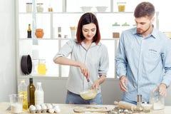 Couples heureux dans l'amour faisant cuire la pâte dans la cuisine Photos stock