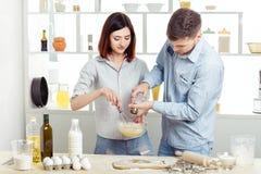 Couples heureux dans l'amour faisant cuire la pâte dans la cuisine Image libre de droits