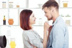 Couples heureux dans l'amour faisant cuire la pâte dans la cuisine Photographie stock libre de droits