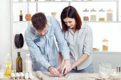 Couples heureux dans l'amour faisant cuire la pâte et faisant des biscuits utilisant des formes dans la cuisine Photos libres de droits