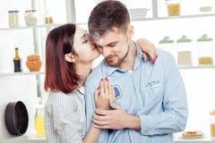 Couples heureux dans l'amour faisant cuire la pâte et l'embrassant dans la cuisine Photos libres de droits