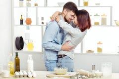 Couples heureux dans l'amour faisant cuire la pâte et l'embrassant dans la cuisine Photo libre de droits