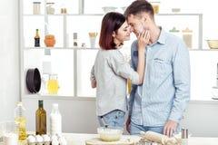 Couples heureux dans l'amour faisant cuire la pâte et l'embrassant dans la cuisine Photographie stock libre de droits