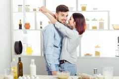 Couples heureux dans l'amour faisant cuire la pâte et l'embrassant dans la cuisine Images stock