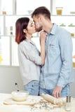 Couples heureux dans l'amour faisant cuire la pâte et l'embrassant dans la cuisine Image libre de droits