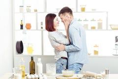 Couples heureux dans l'amour faisant cuire la pâte et l'embrassant dans la cuisine Photographie stock