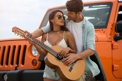 Couples heureux dans l'amour jouant sur une guitare ensemble Photographie stock