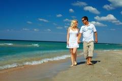 Couples heureux dans l'amour marchant sur le rivage de mer Images libres de droits