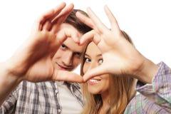 Couples heureux dans l'amour montrant le coeur Image stock