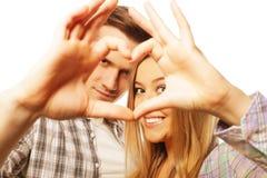 Couples heureux dans l'amour montrant le coeur avec leurs doigts Photos stock