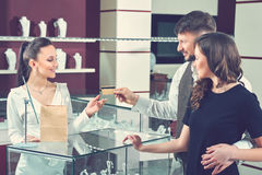 Couples heureux dans l'amour payant avec la carte de crédit au stor de bijoux Images stock
