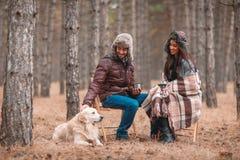 Couples heureux dans l'amour, se reposant dans la forêt d'automne buvant du thé chaud et jouant avec un chien Photographie stock