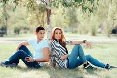 Couples heureux dans l'amour se reposant sous un arbre en parc Image libre de droits