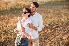 Couples heureux dans l'amour se tenant au champ pendant le coucher du soleil Photo stock