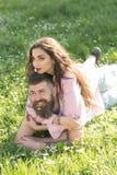 Couples heureux dans l'amour se trouvant sur le pré fleuri tenant les fleurs blanches minuscules dans leurs bouches Homme barbu e Photographie stock libre de droits
