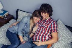 Couples heureux dans l'amour semblant le comprimé électronique sur le lit Photographie stock libre de droits