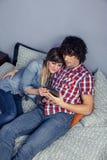 Couples heureux dans l'amour semblant le comprimé électronique sur le lit Photographie stock